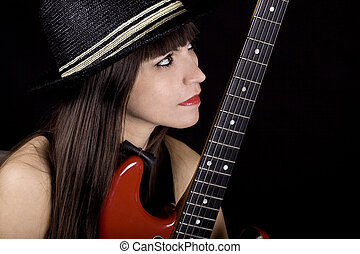 Woman playing R and B on guitar - Brunette with a black hat...