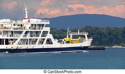 Ferry Boat and Ship on the Sea in front of trees, mountain...