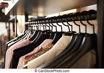 Clothes on hangers in shop.