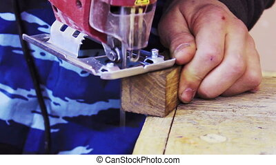 Wood Processing - Woodworking Mans hands cut off a piece of...