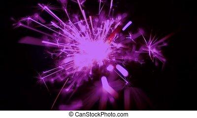 Holiday sparkler burning in macro shot toned in vintage violet color. Holiday firework.  50 FPS Slow Motion. Defocused sparks