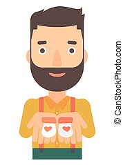 Man holding baby booties. - A hipster man with the beard...