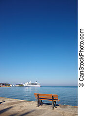 Holiday cruise liner - Small brown ampty bench on the marina...