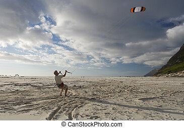 A young man flying a power kite in strong wind - A young...