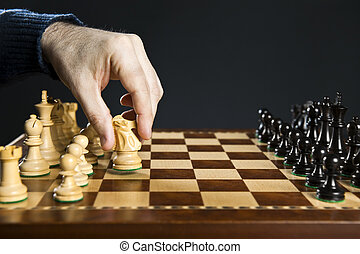 Hand moving knight on chess board - Hand moving a knight...