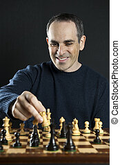Man playing chess - Man moving a chess piece to win the game
