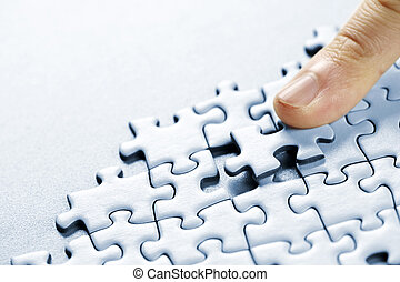 Puzzle pieces - Finger pushing missing puzzle piece into...