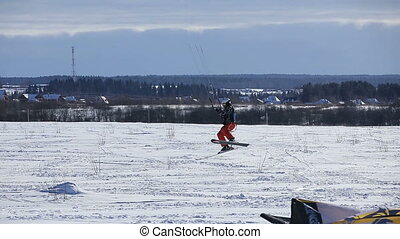 Winter snowkiting on the field. - Man making jump winter...