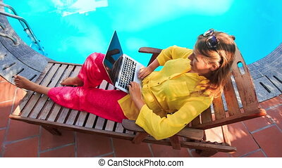 Blond Girl Sits on Folding Chair Works on Laptop by Pool -...