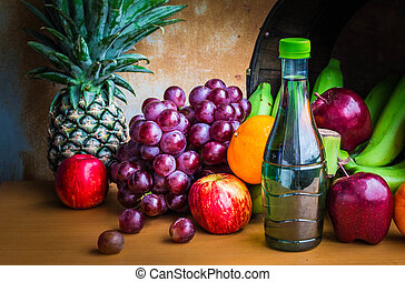 Bottles of juice and fruits on a wooden