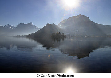 Annecy lake and sun flare - Annecy lake and mountains with...