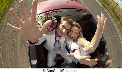 Happy newlyweds in a car - Happy newlyweds in convertible...