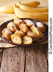 Tasty fried bananas in batter with powdered sugar vertical -...
