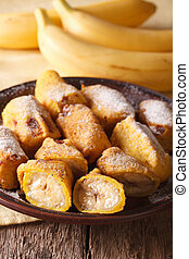Fried bananas sprinkled with powdered sugar close-up...