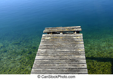 Wooden pontoon and blue water on quiet Annecy lake, France