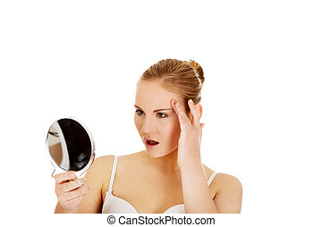 Beautiful shocked woman with a mirror