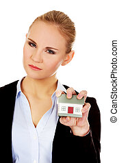 Aggresive business woman crushing small house.