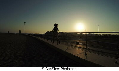Silhouette of walking girl - In sun backlit Olympic Park and...