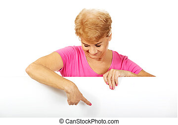 Senior woman pointing for something on empty banner -...