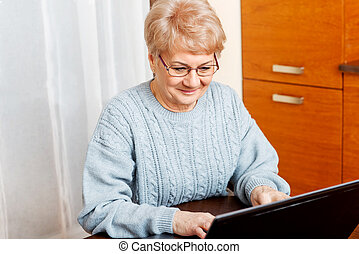 Smile senior sitting at table and using laptop
