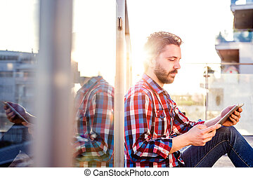 Businessman working from home on tablet, sitting on balcony...