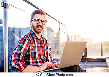 Businessman working from home on laptop, sitting on balcony...