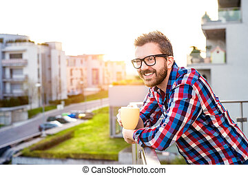 Businessman with cup of coffee standing on balcony, relaxing...