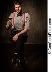 Young handsome old-fashioned bearded man with glass of brandy sitting on dark background.