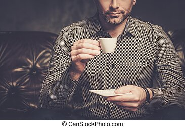 Confident handsome bearded man with cup of coffee sitting on comfortable leather sofa on dark background.