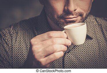 Confident well-groomed bearded man with cup of coffee on...