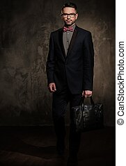 Well-groomed stylish young man with briefcase posing on dark...