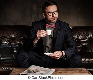 Well-groomed stylish young man with cup of coffee sitting on...