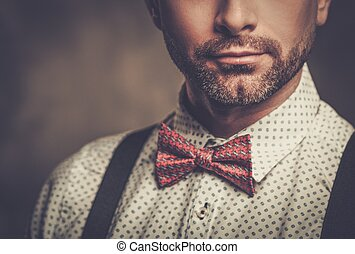 Stylish man with bow tie wearing suspenders and posing on...