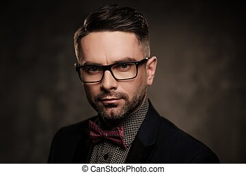 Well-groomed stylish young man with bow tie posing on dark...
