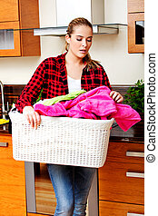 Happy young woman carrying laundry basket in kitchen
