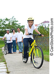 Asian three generation Family On Cycle Ride In Countryside