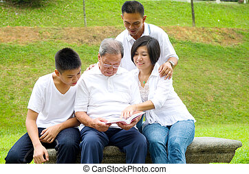 Asian three generation family reading book at outdoor park