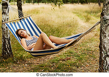 Young woman resting on hammock - Young blonde woman resting...