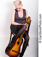 Drunken blonde woman sitting on a chair, lowered stockings legs hugging guitar