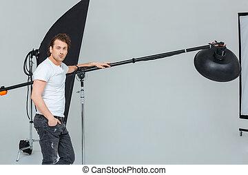 Male photographer preparing lighting equipment - Handsome...