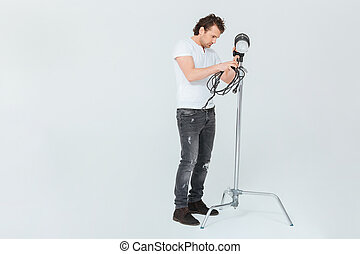 Male photographer preparing lighting equipment isolated on a...