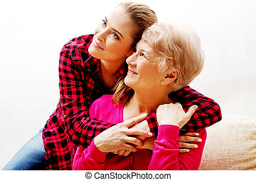 Senior woman with granddaughter or daughter hugging on...