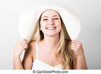 beautiful funny young blonde woman in white tank top and a large white hat smiling