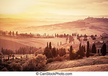 Wonderful Tuscany landscape with cypress trees, farms and small medieval towns, Italy. Vintage sunset