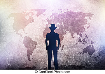 Silhouette of a man in hat standing in front of world map on grunge concrete wall
