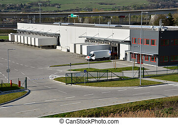 Modern logistics center, white van and trailers standingon...