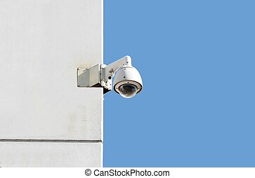 surveillance camera at a white wall with blue sky background