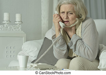 Mature woman calling doctor - Portrait of a sick mature...
