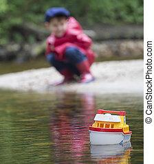 small boy sailing his tug boat.