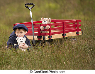 small male child sitting beside a wagon holding his teddy...